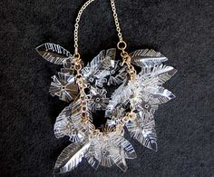 eco sparkly recycled plastic jewelry by Kumvana Gomani. This innovative Swedish designer has found a a great way to turn recycled soda and water bottles into snowflakes and crystallized leaves that radiate green chic bling.