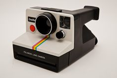 """Polaroid OneStep Classic White Rainbow SX70 Instant Camera Tested - Working - Vintage 80s SX-70This is the famous Polaroid OneStep Classic white with rainbow stripe camera with a """"fixed focus"""" plastic lens. This camera was know as the Polaroid 1000 camera in the UK.Additional features include:- 1 element plastic lens with fixed aperture (103mm, f14.6)- 4ft minimum focus distance.- exposure compensation dial around electric eye- uses Polaroid SX-70 film, Impossible Project PX-100 Silver Shade…"""