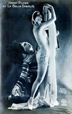 Alfred Noyer. The topless performer La Belle Dherlys, wearing a long string of pearls around her head, and the American dancer Harry Pilcer during a performance at the Revue du Casino de Paris.1st March 1921. Via getty