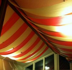 Circus Tent - Drape your wedding venue ceiling in striped carnival colours that creates the illusion that you're inside a circus tent. From the corners of the ceiling and meeting in the centre, drape red and white striped fabric or table cloths that are cut into broad strips.