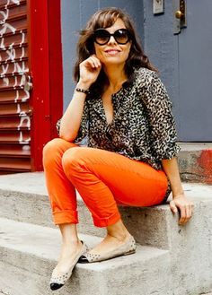 a neutral leopard print blouse over orange skinny colored jeans with ballet flats