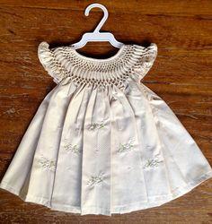 Vestido em popeline bege, com pequeninos poás brancos, 100% algodão, com pala em ponto smock (casinha de abelha) e bordado à mão. Tamanho: P: 0 a 6 meses M: 6 a 12 meses