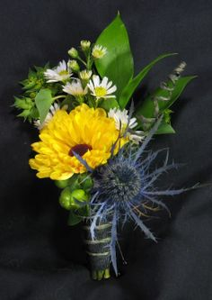Wildflower boutonniere created with blue thistle, white aster, and sunflowery looking Viking poms.#sunflowerwedding #wildflowerwedding #sunflowers #wildflowers #summerwedding