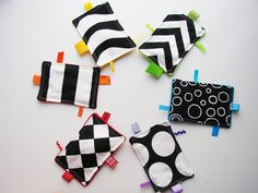 "fabric sensory ""cards"" - High-contrast black and white on one side, 1 color of the rainbow on the other. Ribbon tags, different fabrics for sensory experiences, and different sound shakers inside each. Can be hung from stroller or carseat with ring."