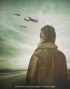 Sandra Cunningham Woman wearing leather jacket and cap looking at planes fly by