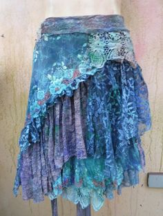 bohemian skirt,tattered skirt, gypsy skirt, boho skirt, wrap skirt, wedding, bridal, bridesmaid, gypsy, belly dance, mori girl, lace skirt, if youd like one in your size let me know and i shall create...  she,s gothic shabby skirt/belt in mottles hues of blue/green/burgundy/purple kissed with ruffles of lace and netting and embellished with beaded bridal laces,roses,rose trims and shabby roses adding to her charm... 48 across and can wrap around and over lap with belt hole and loop so will…
