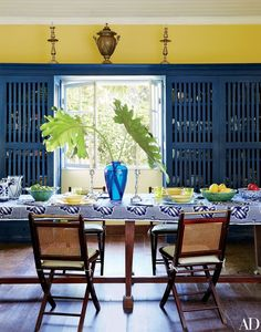 Antique English candlesticks and an African cloth dress the dining room table | archdigest.com