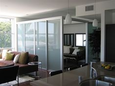 L-shape sliding room divider creates additional private space without full construction and lets in tons of natural light at the same time! Made by The Sliding Door Company.