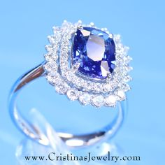 This exquisite ring boasts a 3.06 carat rectangular cushion cut Ceylon Blue Sapphire, the most rare and treasured color tone of all sapphires.  Surrounding the sapphire, are 1.02 carats (total weight) of virtually perfect diamonds in an elegant double halo.  Though distinctly different, this ring echoes similarities to the world famous Princess Diana engagement ring.   Set in 18 Karat white gold, the ring is an heirloom quality treasure that will perfectly accessorize ANY social event…