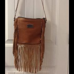 """Cool fringed cross body bag Golden caramel, embellished with studs and 9"""" fringed crossbody  has adjustable cross body shoulder straps, 4 inside pockets and protective base cleats. Such a cool bag by Shyanne. In perfect condition. Carried once. Shyanne Bags Crossbody Bags"""