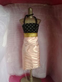 Harumika design #9:tis design is a lovely modern day style dress a black and white polka dot tube top with a gold shiny belt and a peach shiny skirt.