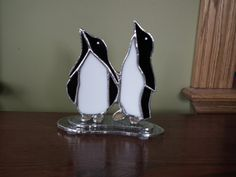Two penguins in stained glass on an ice floe.
