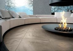 large round sunken seating area with hanging fireplace
