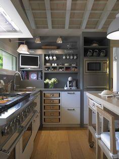 Una cocina modera y actual de 21 metros cuadrados. De planta rectangular, cuenta con isla central móvil.
