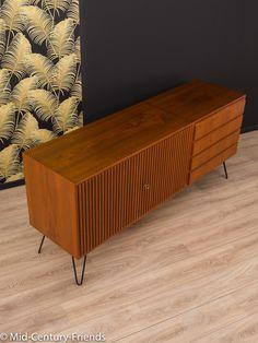 Klassisches Sideboard aus den 1950er Jahren. Korpus in Teak Furnier mit vier Schubladen, zwei wundervollen Schranktüren und neuen, zeittypischen Hairpin-Legs in Schwarz.  Qualitätsmerkmale: -...
