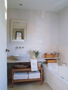 00164410 O. Baño con encimera y bañera de mármol en tonos claros y un pequeño mueble de madera bajo el lavabo_00164410 O