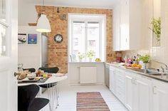 Aranżacja białej kuchni skandynawskiej ze ścianą z czerwo9nej cegły i białą pidłogą