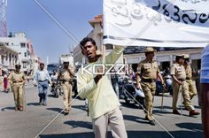 man holding sign - A man holds a sign and is followed by guards in India