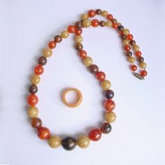 """This great vintage marbled plastic graduated bead necklace is paired with a coordinating marbled butterscotch Bakelite ring. The necklace is 24"""" long; the largest bead in the center is 18mm wide (a li"""