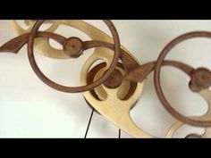Wood That Works -- kinetic wooden sculptures that hang on a wall, by David C. Roy. Wind one up, runs for many hours.