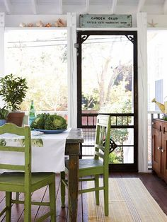 indoor country inspired porch. Those green chairs are fierce. I also love the black screen door.