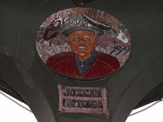"""JOSE ANTONIO URTIAGA BAYÓN """"JOXEAN"""" (Santurtzi, 1926 - Santurtzi, 2015). Mural discoidal realizado en la técnica del mosaico de tesela cerámica y modelado en relieve por Paco Presa Merodio (Torrelavega, 1961 -). Ubicado en 2008 en el interior del kiosco de música para homenajear a este popular arraunlari. Los motivos decorativos que rodean su busto nos remiten al mundo de las regatas de traineras y al club Itxasoko Ama."""