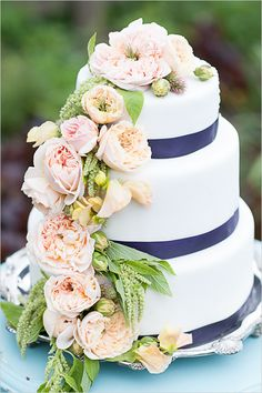 a fresh floral cascade is a lovely accent to this simple cake. the navy blue ribbon compliments the peach and green from the florals really nicely.