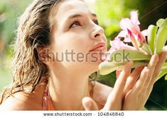 Close up profile view of a young attractive girl smelling a rose-bay flower in an exotic garden.