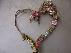 guirlanda de coração feita de cipó, com flores de bibra de bananeira e fuxico, totalmente feita a mão.