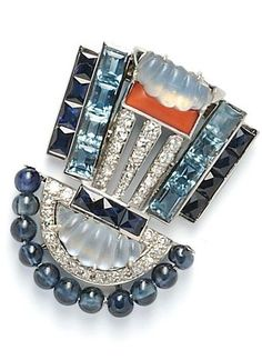 Art Deco Platinum Gem-set Clip Brooch, Oscar Heyman, of geometric form, set with carved moonstones, channel-set French-cut sapphires and step-cut aquamarines, buff-top coral accent, and sapphire beads, further set with full- and single-cut diamonds, engraved gallery, lg. 1 1/2 in., (chips to moonstones).