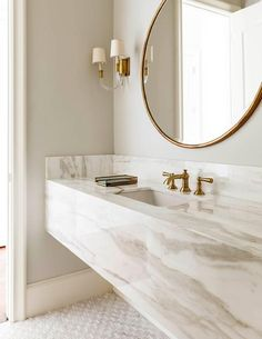 White and gold bathroom with marble floating vanity. Chic bathroom boasts a grey and white marble floating vanity sink, suspended over a marble mosaic .