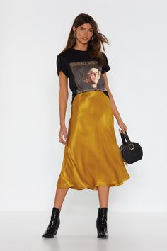 Raise hell. This skirt comes in satin and features a midi silhouette, elasticized waist, and bias cut hem.