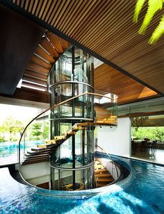 The Botanica Residence by GUZ Architects Stairs made from glass, steel, and wood, have been designed as a sculptural element in this modern house, while a wood slat ceiling and the water detail add a natural touch. Steel Stairs Design, Spiral Stairs Design, Spiral Staircase, Staircase Design, Wood Stairs, Stairs Architecture, Architecture Design, Glass Elevator, Elevator In House