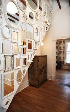 Thrift store mirrors are painted the same white color and turned into a stunning gallery wall art installation on a hallway staircase wall. From bright designlab via Houzz.