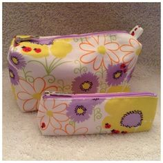 """SpecialLADYBUG Cosmetic Bag  2pc. Set Made by: Clinique 2pc. Set. Lavender orange yellow on White with Lady bug Design. Bags are fully lined and new... Never used. Large bag measures: 5""""Tall X 8""""Wide X2.75""""Thick with an 8""""Zipper. Small bag measures: 3""""Tall X8""""Wide X 2""""Thick. Thank you for browsing my closet. Clinique Bags Cosmetic Bags & Cases"""