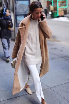 Minimal classic neutral look in beige and camel tones. White trousers, beige sweater and long teddy bear coat in camel.