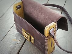 Original shoulder bag for modern life style. Made of natural dark brown leather and distressed oak wood. The front panel is carved and distressed carefully. size: 26x22x6 cm The side panels are made of oak wood carefully distressed, sanded and finished with non toxic water based lacquer.