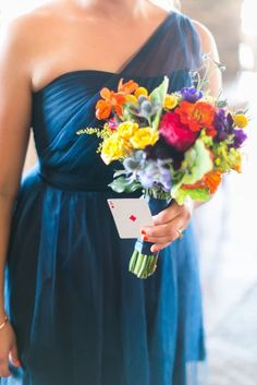 Bridesmaids bouquets of florals in yellow, orange, red, purple and blue. Navy bridesmaids dresses.