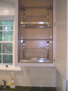 I had the bottom of a standard wall cabinet cut out and installed 2 ikea drying racks inside. I then asked the countertop installers to grind grooves and a slight slant into the granite allowing water dripping from the drying cabinet to run directly into the sink.