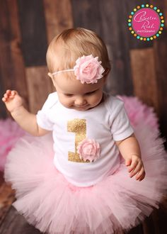 The perfect first birthday outfit for the little girl in your life. With this purchase you will receive a 100% cotton onesie, a high quality tutu and matching headband. Details: Onesie This sweet outfit comes with a white short sleeved onesie made from 100% cotton featuring a gold glitter 1. (Glitter is non shedding | yay no mess!) The numerical 1 is perfectly adorned with a light pink chiffon flower which is securely and professionally sewn on. It will never come off when tugged with little…