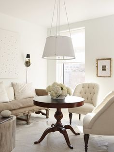 Ivory and beige decor with stark white walls and dark wood center table with a lovely floral arrangement sitting atop.
