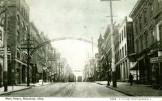 "Photo looking south on North Main Street from Temple Court in 1910. The Masonic Lodge/Post Office are off to the left. Louis Sam's Laundry is to the right, on the west side of the street. Streetlight arches arc over the street and three streetcars pass one another just south of the North Main - Fourth Street intersection. Wall posters advertise ""the Drummer Boy of Shiloh."""