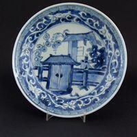 MING PORCELAIN. TIANQI or CHONGZHEN c.1620 - 1640 Transitional Porcelain A Ming Blue and White Ko-Sometsuke Porcelain Dish, Tianqi (1621-1627) or Chongzhen (1627-1644). Decorated with a Door Leading into a Court Yard with a Scholar Desk (a Brushpot is on the table) a Scholar`s Rock and Banana Plants. The Cavetto Painted with a Meandering Lotus Scroll in White Against a Blue Background. The Rim with a `Greek Key` Border.