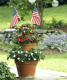 A tower of potted plants marks a tread-on-me path. Gather three pots and saucers. Fill each pot with soil; stack with saucers in between. Tuck in-palette impatiens into the soil; pop in a pair of flags.  - GoodHousekeeping.com