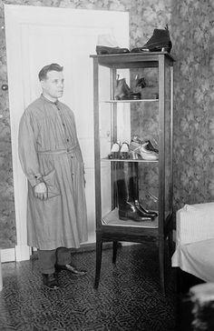 Työasuinen suutarimestari seisoo esittelyssä kääntyneenä kenkävitriininsä puoleen Iso Hämeenkatu 2:ssa. Vitriinissä on esillä saappaat ja naisten ja miesten kenkiä ja sen päällä on kahdet vastakkain asetetut naisten nilkkurit. Kuvaaja: H. Attila, 1929. TMK.