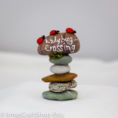 Adorable Ladybug Crossing Rock Sign  3 1/2 tall x 2 1/8 wide x 1 1/2 deep  made of rocks, moss, and wooden ladybugs, acrylic paint     BRIGHTEN UP