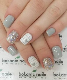 Gray, white and silver nail art with embellishments. Light and cheery looking nail art with stripes and heart shapes, additional sequins have also been placed on top of the silver glitter polish.