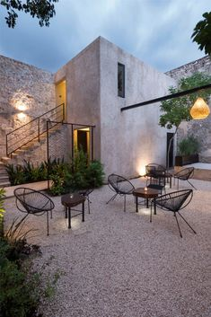 the most beautiful gravel courtyard, with exposed stone and black iron chairs