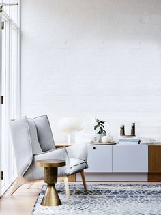Gorgeous neutral gray armchair next to console with white lamp and marble clock | Brighton Residence by Simone Haag | NONAGON.style