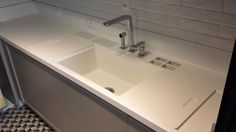 Cozinha em Corian Glacier White, com nicho equipado, cuba em Corian e tampas deslizantes.